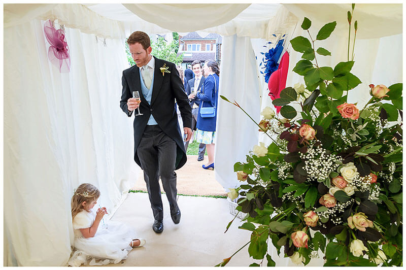 flower girls finnishing her drink sat on floor of marquee as usher walks past