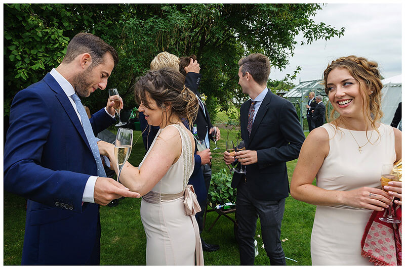 Final adjustments for bridesmaids boyfriend during Village Wedding reception