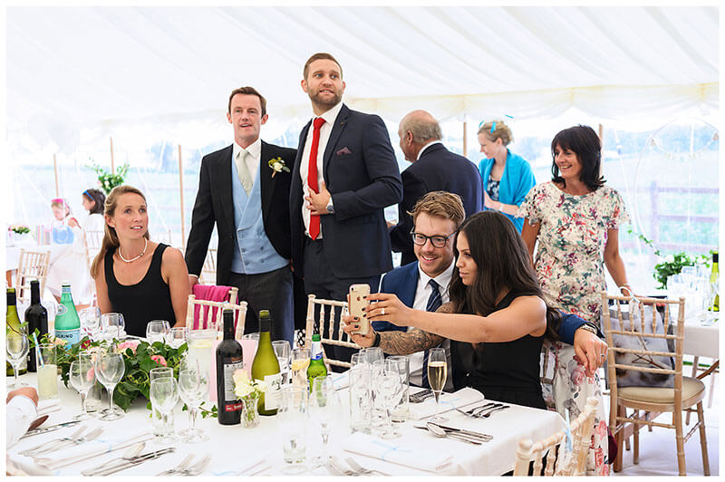 Couple taking a selfie sat at table whilst other guests look for their seats