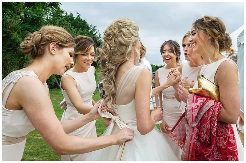 Smiling and laughing Bridesmaids surrounding bride two do up brides ribbon whilst others hold brides hand