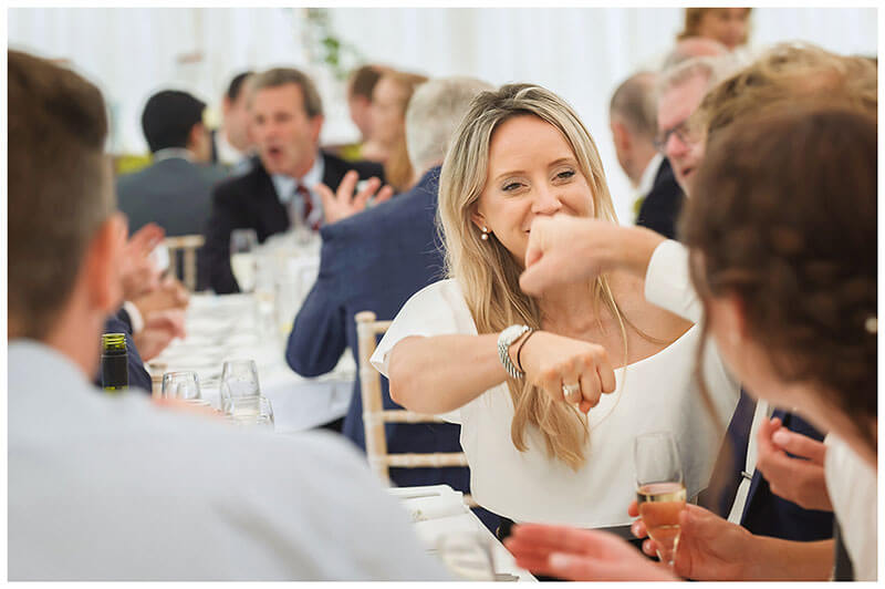 Two guest pump fists whilst sat at dining table