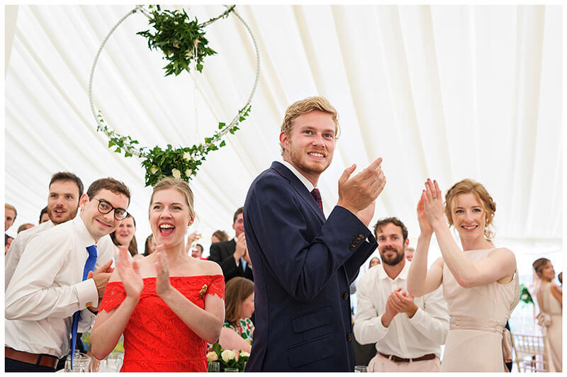 Guest cheer and appluad bride groom on entering marquee for wedding breakfast at Chrishall Cambridgeshire Village marquee Wedding