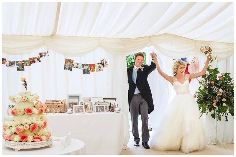 Happy Bride groom raise arms in celebration as they enter marquee