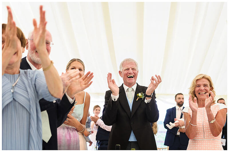 Smiling guests applaud bride groom as they enter marquee for reception party
