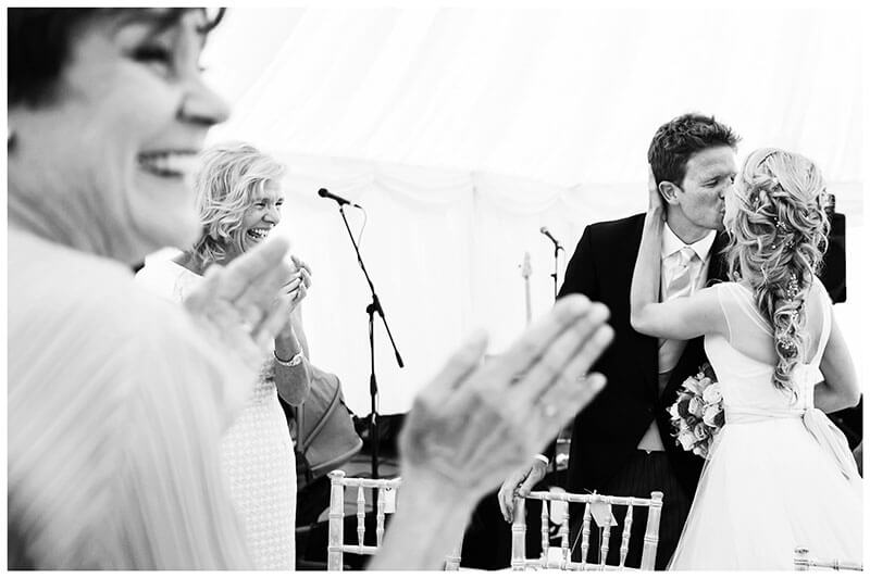 Bride kisses groom applauded by guests as they arrive at head table marquee Village Wedding reception
