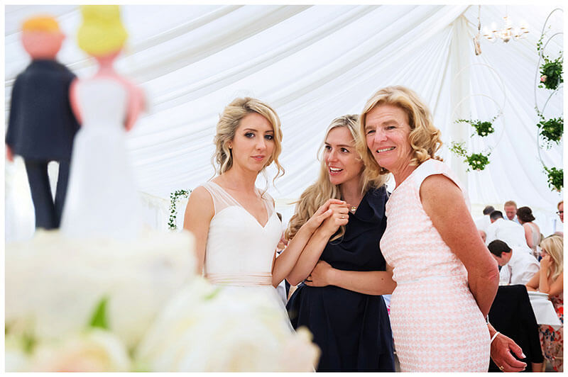 Bride holds hands with lady whilst looking at wedding cake with mother in law
