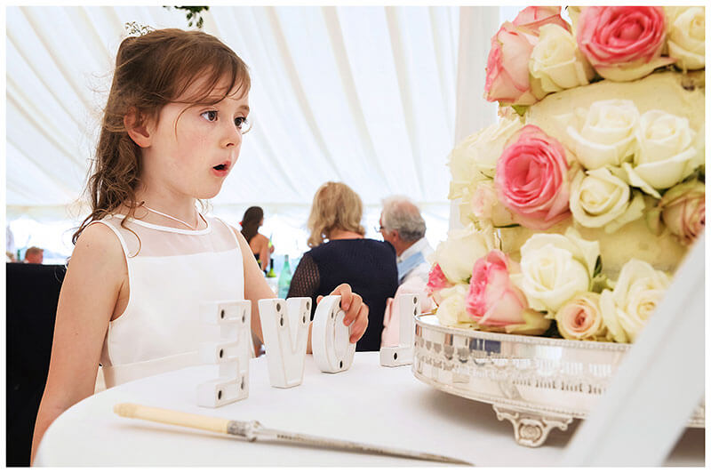 Flower girls wow at wedding cake holds letter O of the word love on cake table