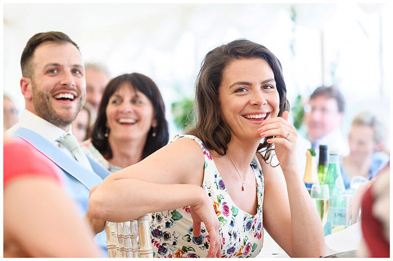 laughing guests during speeches held in marquee