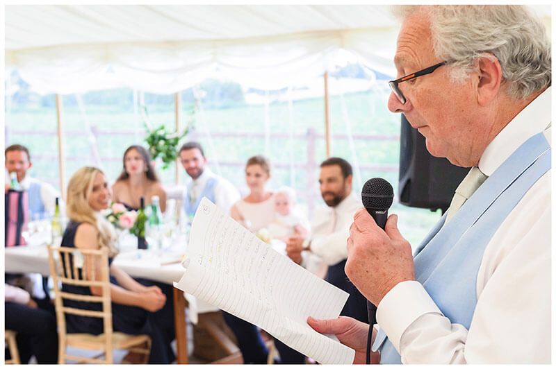 Father of bride reading speech watched by guests inside marquee