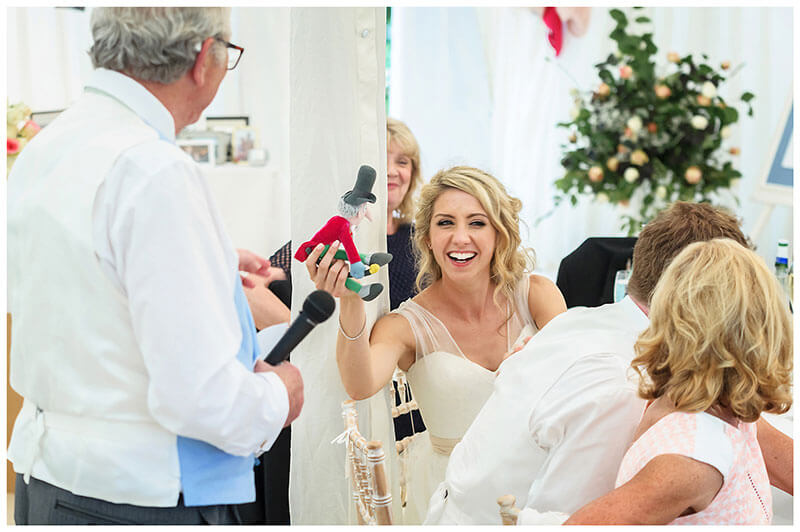 Smiling bride as she is handed a childhood toy during fathers speech