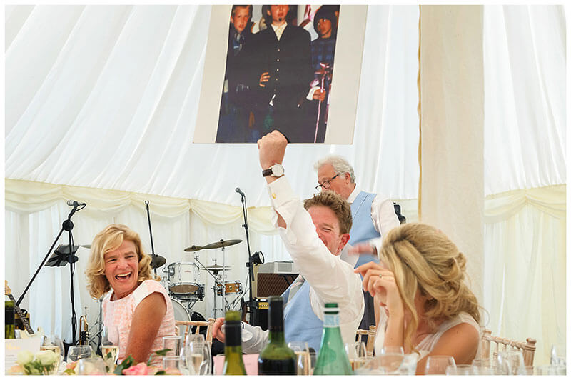 Groom holds up large photo of him dressed up bride embarressed mother laughing
