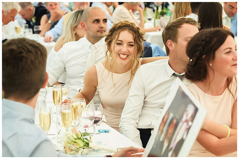 Smiling bridesmaid looking at large photo of groom during speeches
