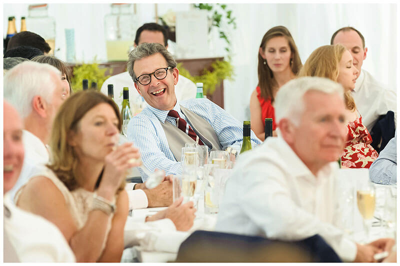 laughing male guest in glasses during speeches