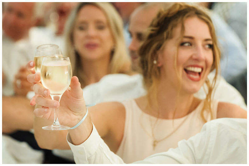 cheers raising of wine glasses smiling bridesmaid