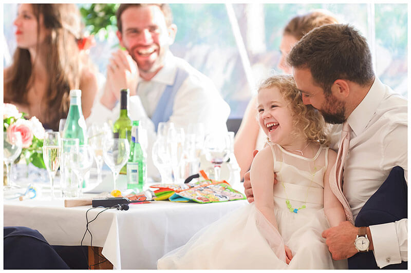 laughing flower girl sat in fathers lap during speeches
