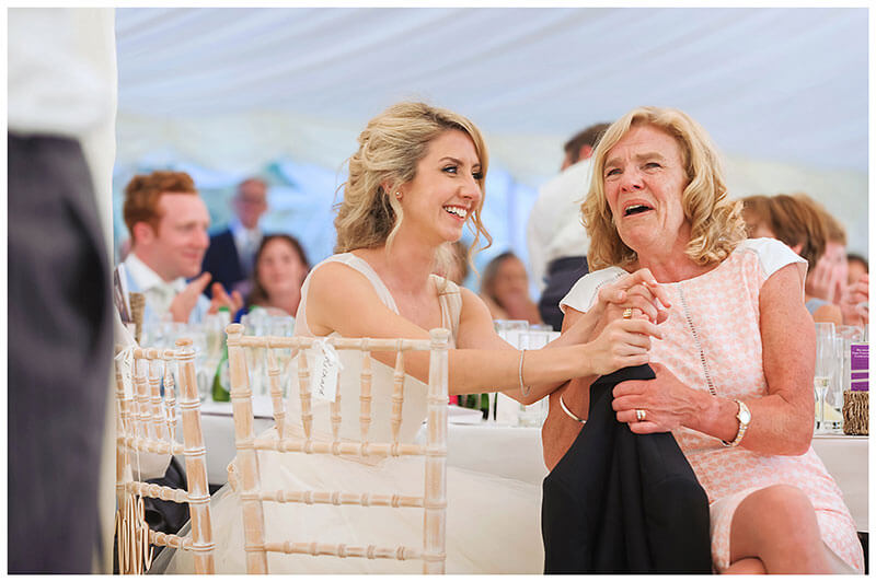 Bride smiles at grooms mother whilst holding her hand during grooms speech