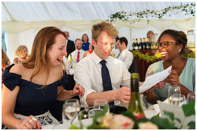Guests pulling faces at photos during speeches Chrishall Cambridgeshire Village Wedding