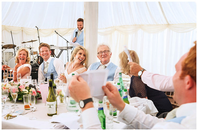 Head table laughing at photos during bestmans speech at Chrishall Cambridgeshire Village Wedding