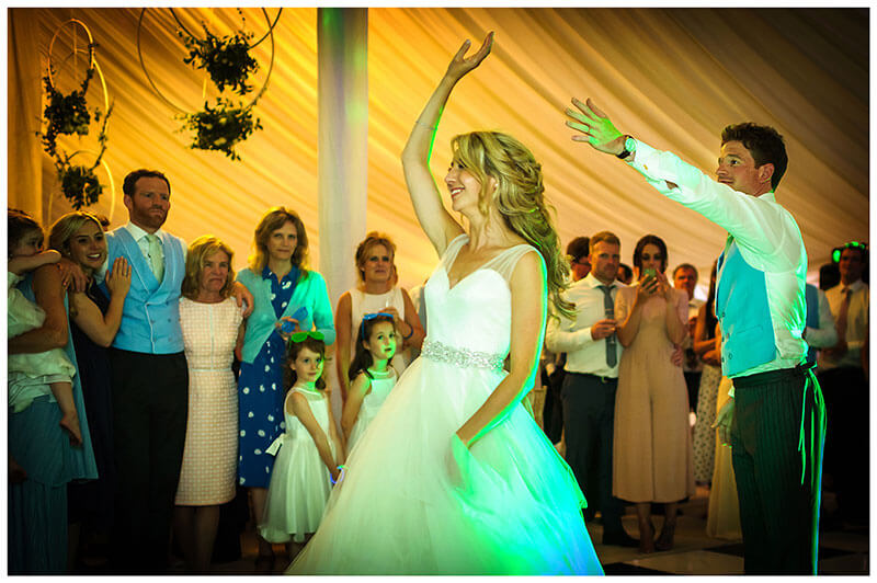 Bride twirls and groom lets go of her hand during first dance in marquee