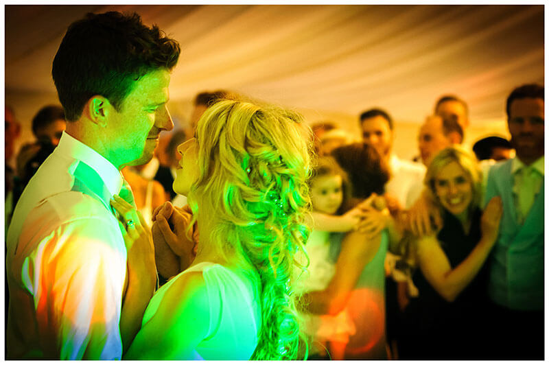 Bride groom embrace during first dance watched by guests
