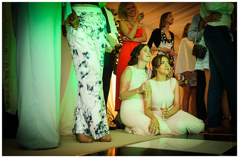 bridesmaids sitting on floor as bride groom do their first dance inside marquee