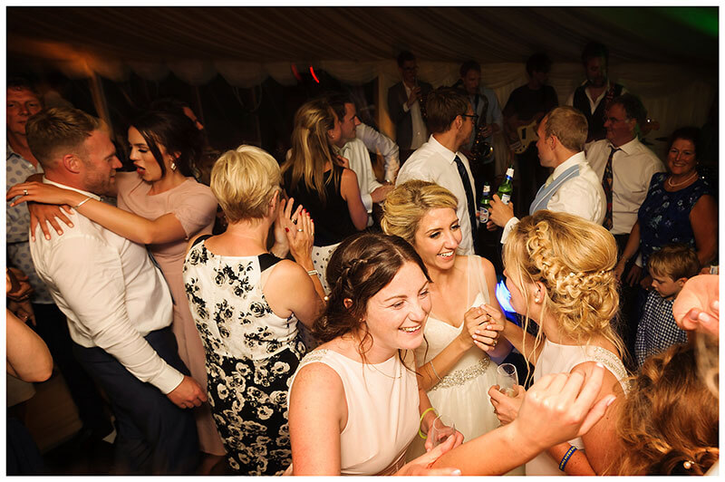 Brid eand bridesmaids on the packed dance floor