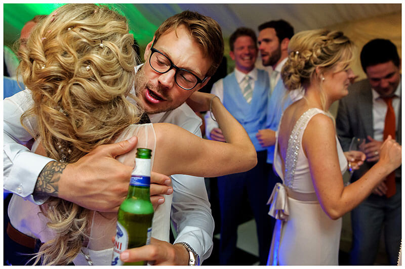 Giving the bride a hug on the dance floor while holding a bottle of beer
