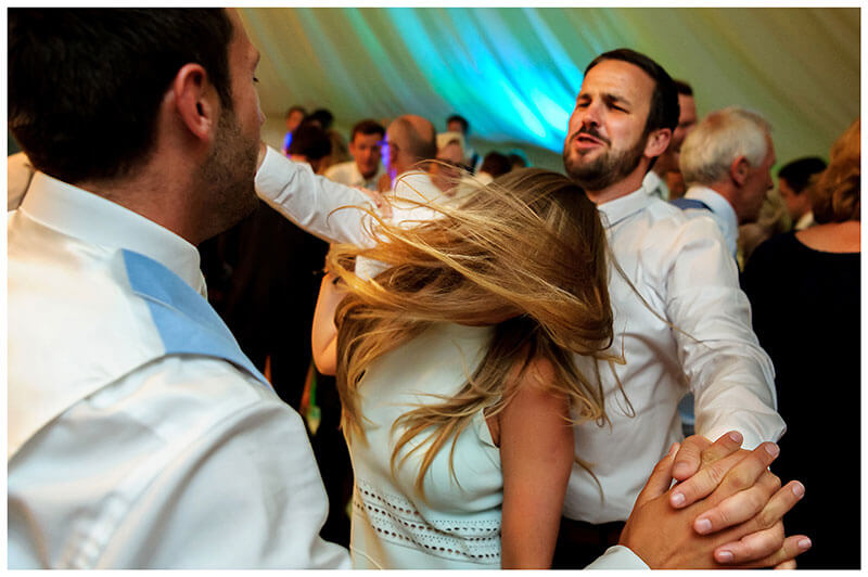 Two guys hold hands as they dance around lady who is swishing her hair on the dance floor