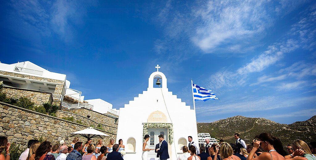 destination wedding photographer bride groom exchange rings in front of white chapel on the greek island of Mykonos