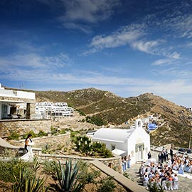 Bride and her farter walking down steps for ceremony in front of white chapel capured by International destination wedding photographer at Mykonos wedding