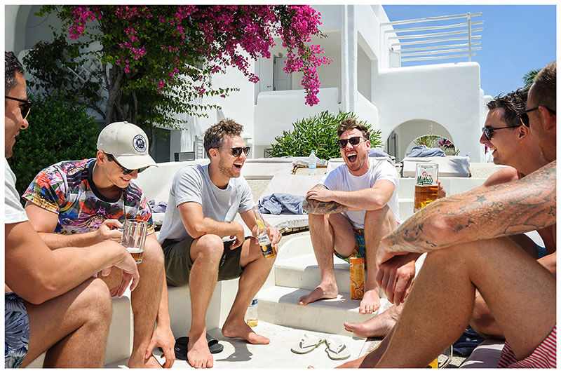 Groom having a laugh and a drink with his male friends at the pools side of the Andronikos Boutique Hotel Mykonos prior to getting ready for the ceremony