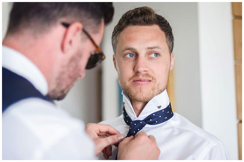 Andronikos Boutique Hotel Mykonos groom getting help with his tie during preparations