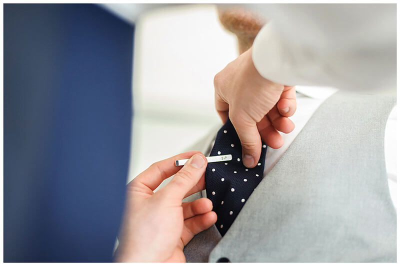 Tie pin being placed into position during groom prep at Andronikos Boutique Hotel Mykonos