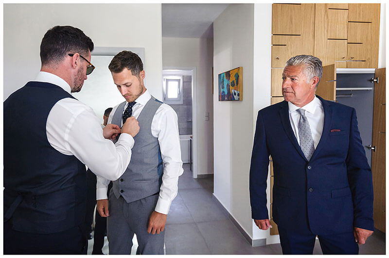 Grooms Father watches usher help Groom with his tie pin during grooms prep at Andronikos Boutique Hotel Mykonos