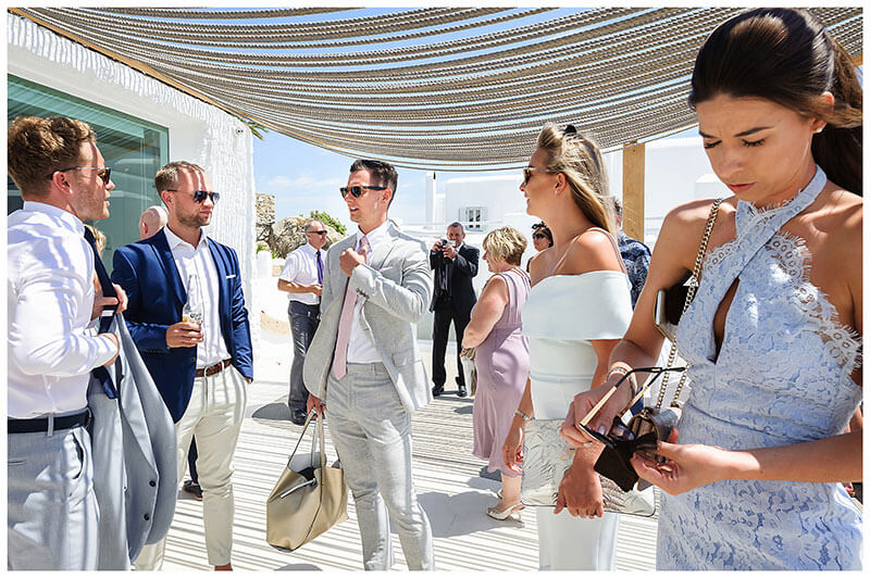 Lots of wedding guests under rope canopy talking as they wait for transport to the wedding ceremony at Andronikos Boutique Hotel Mykonos
