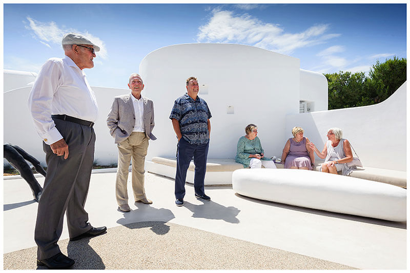 Elderly gentlemen standing in the sun and ladies sitting in the shade at Andronikos Boutique Hotel Mykonos