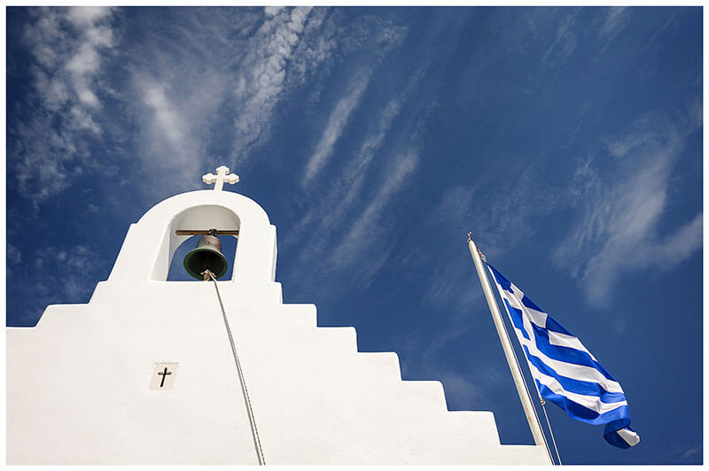 White chapel tower with bell and Greek flag flying against a deep blue sky