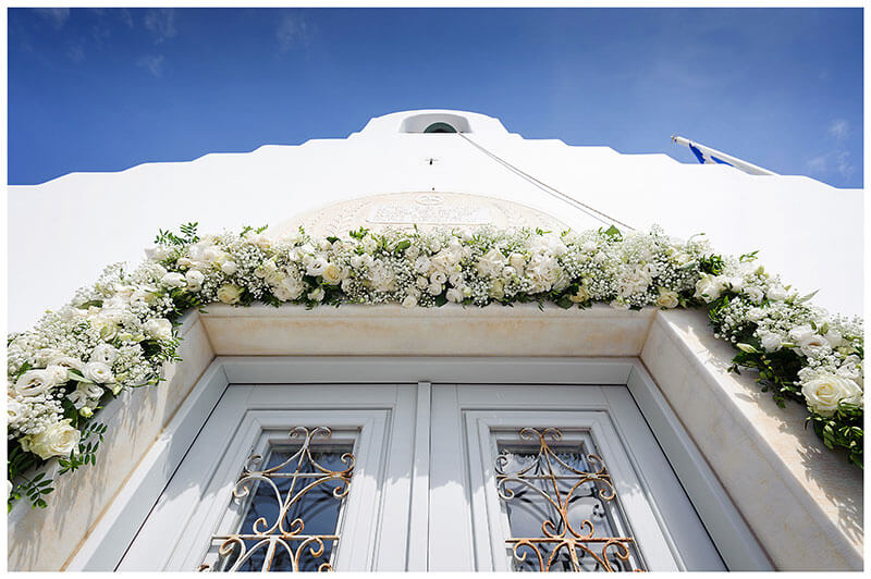 Flower decoration around light blue door of White chapel at Royal Myconian Resort Mykonos