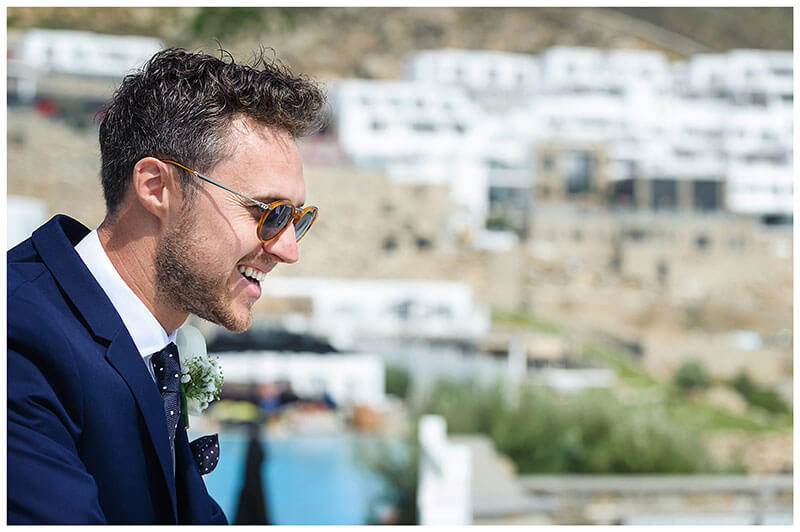 groom in sunglasses smiling whilst looking at view of Royal Myconian Resort