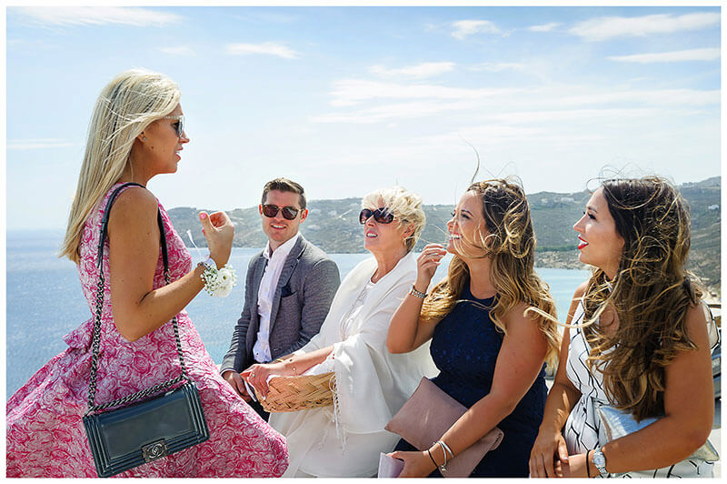 Wedding guests sitting on wall talk to lady in pink dress before wedding ceremony at Royal Myconian Resort Mykonos