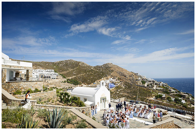 Guests watchong bride walking down steps towards white chapel and her groom at Royal Myconian Resort Mykonos