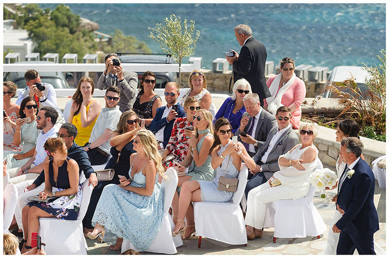 Wedding guests taking photo of bride as she arrive to walk down aisle for wedding ceremony at Royal Myconian Resort Mykonos