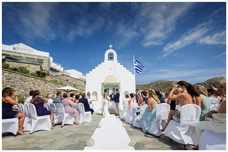 Guest watching wedding ceremony in front of white chapel at Royal Myconian Resort Mykonos