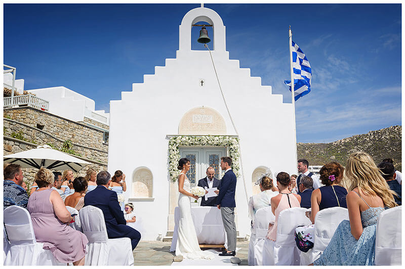 Bride looking at her groom during wedding ceremony in front of white chapel at Royal Myconian Resort Mykonos