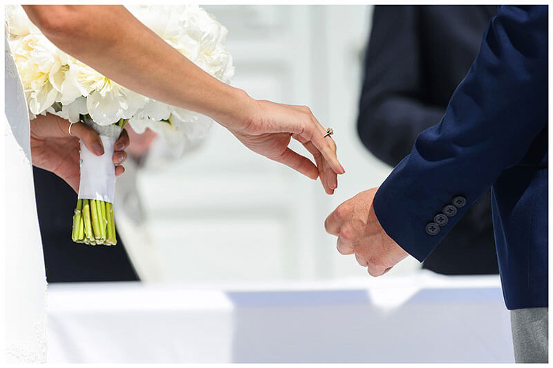 Bride about to place her hand in grooms whilst she holds her white bouquet in her other hand