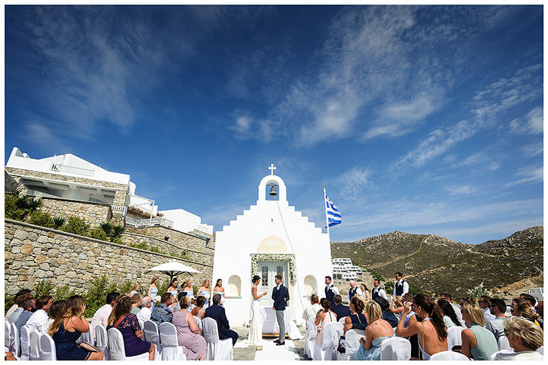 bride reading her vows to her groom in front of white chapel under blue sky watched by seated guests at Royal Myconian Resort Mykonos