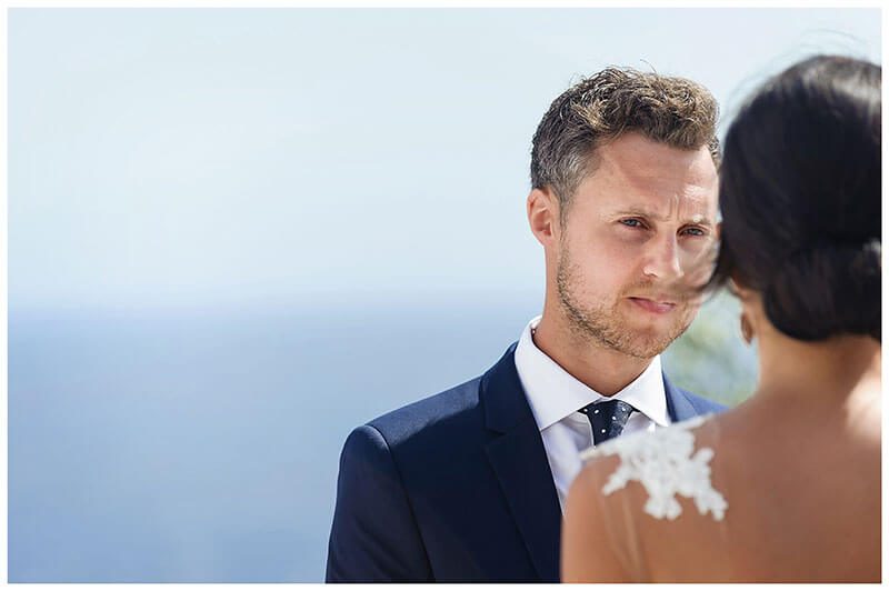 Groom looking at his bride during wedding ceremony at Royal Myconian Resort Mykonos
