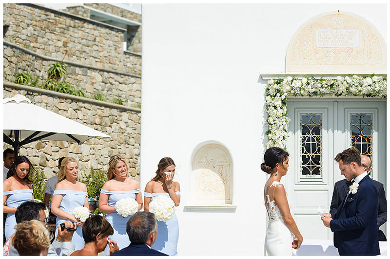 Groom reads his vows to his bride, bridesmaid and female guest wipe away a tears at Royal Myconian Resort Mykonos wedding ceremony