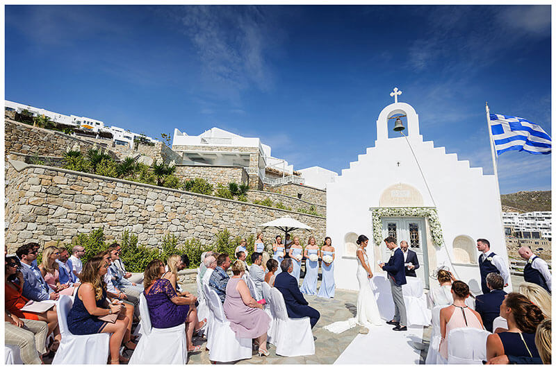 Wedding guests watching groom read his vows in fron tof white chapel under blue sky at Royal Myconian Resort Mykonos