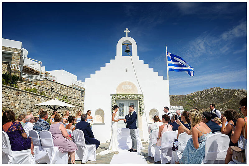 Royal Myconian Resort Mykonos wedding ceremony Bride groom exchange weeding rings in front of white chapel with greek flag flying under a blue sky